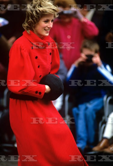 Wearing a Caroline Charles bright red coat and black muff